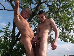 Venerable man sucks twink's cock in outdoor gay play